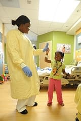An adult holds the hand of a child in a hospital room